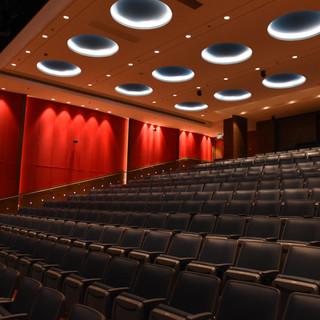 מבט מהצד על האודיטוריום, האור על הקירות האדומים נותן אשליה של מסך תיאטרון קלאסי מקטיפה