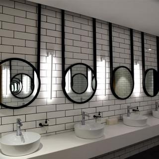חדר שירותי הגברים. גופי תאורה אורכיים בין המראות