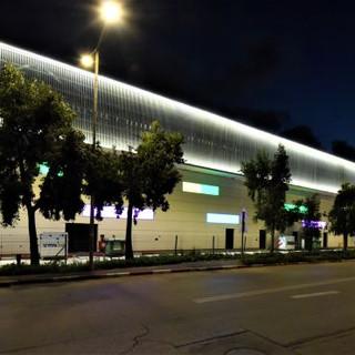 חלקו האחורי של מבנה מתחם הקניות מואר בפסי LED, המדגישים את המבנה