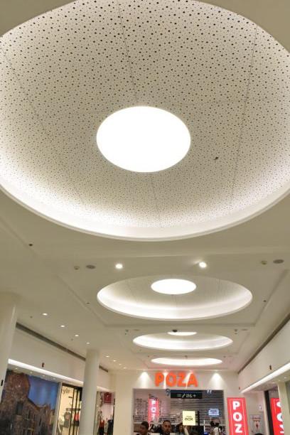 עיגולים של אור על תקרת הקניון, מחישוק של אור, ובמרכזו גוף תאורה עגול, חלבי, שקוע תקרה
