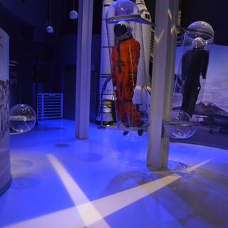 """אולם התצוגה. מעבורת החלל של אילן רמון ז""""ל אור כחול על הרצפה, נחתך באלומות אור בהירות, היוצרות הצלבה על הרצפה."""