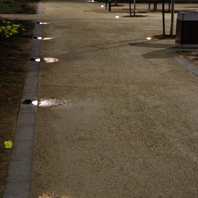 גופי תאורה צמודי רצפה, ממוקמים במרחקים שווים, ויוצרים פסי אור אחידים על שביל הולכי הרגל