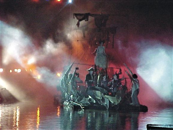 רפסודה עם שחקנים-רקנים מתקדמת על פני המים. האור סגלגל כתום