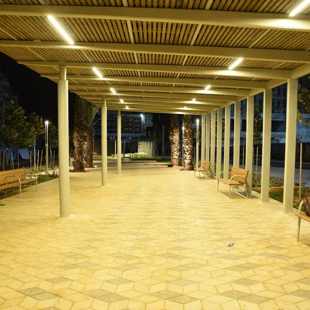 שביל מקורה - ספספלי עץ, גופי תאורה ארוכים וסימטריים מעל