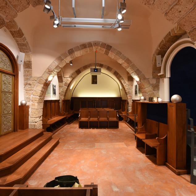 מבט כולל על בית הכנסת, תאורה בלתי ישירה על הקירות, וכלפי התקרה יוצרת אווירה נעימה וייחודית