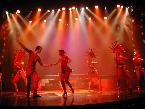 אלומות אור צבעוניות על הבמה, יוצרות עומק ועניין. רקדנים על הבמה.