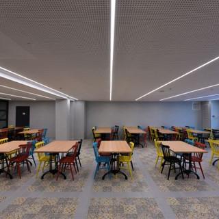חדר האוכל המשני. כיסאות צבעוניים, גופי תאורה שקועים בתקרה.