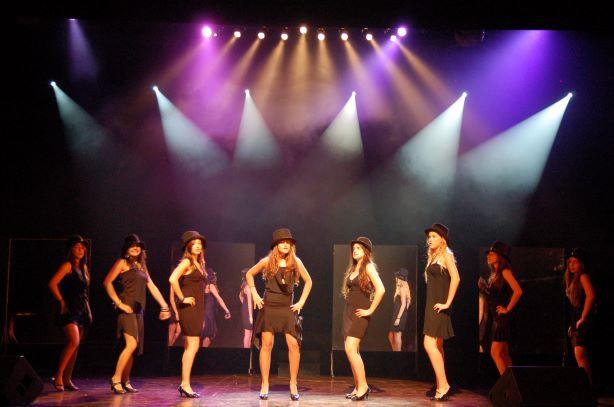 קאסט השחקניות במרכז, מעליהן 2 שטים של אלומות אור בקוטר שונה, ותאורת שטיפה של צבע