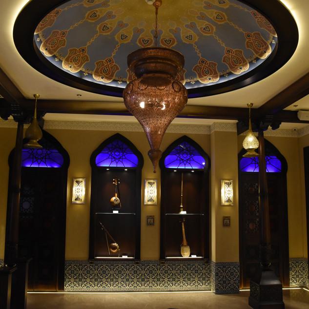 תמונה של כל החלל עם חישוק-האור. ויטרינות תצוגה עם כלי נגיה, זכוכית כחולה מעל, וגופי תאורה על הקיר