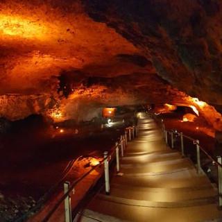 תאורה ממוקדת במרכז גרם המדרגות המוליכה את העין אל עומק המערה. קירות המערה מוארים בכתמי צבע