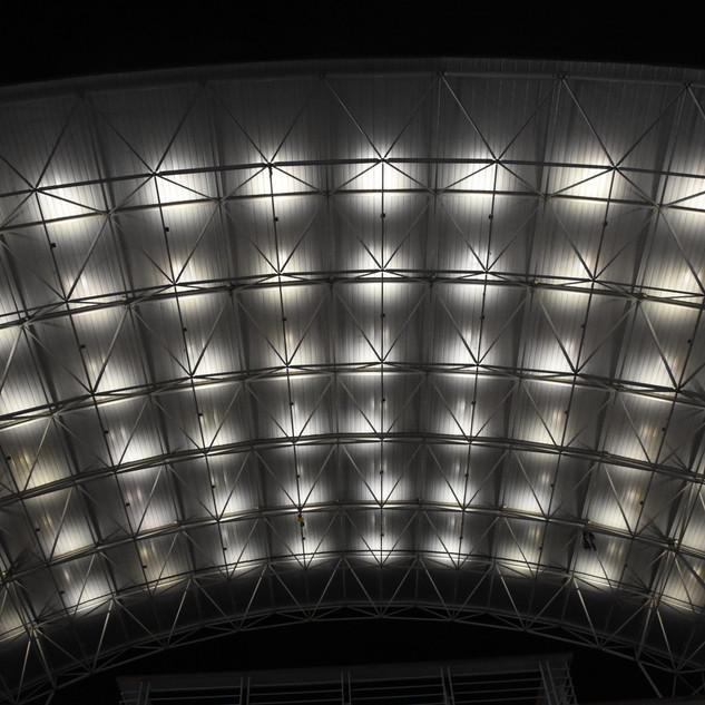 תקרת מבנה אולם ספורט, מוארת באור לא ישיר, הנותן אפקט של עיגולים אור בשמיים