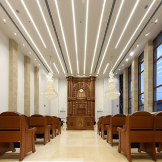 החלל המרכזי של בית הכנסת, גופי תאורה שקועים וארוכים בתקרה.