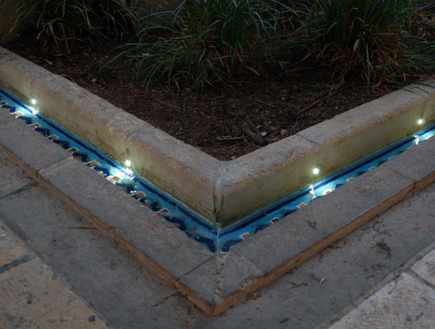 תמונת תקריב של פינת הבריכה. שילוב גופי התאורה בדופן האבן העתיקה.