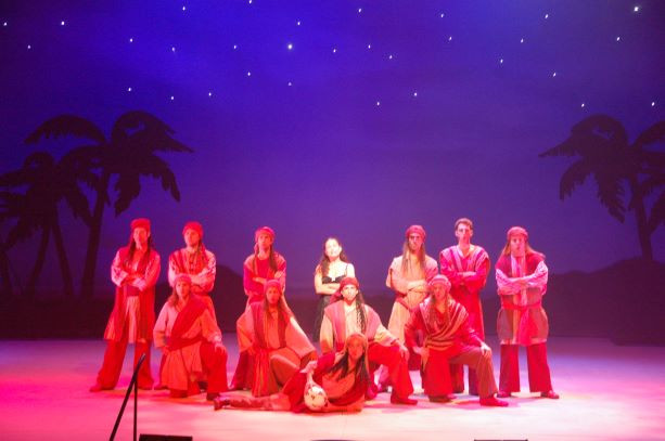 עיגול של אור ממקד את השחקנים. בעומק צללית של עצי דלק, ושמיים מלאי כוכבים
