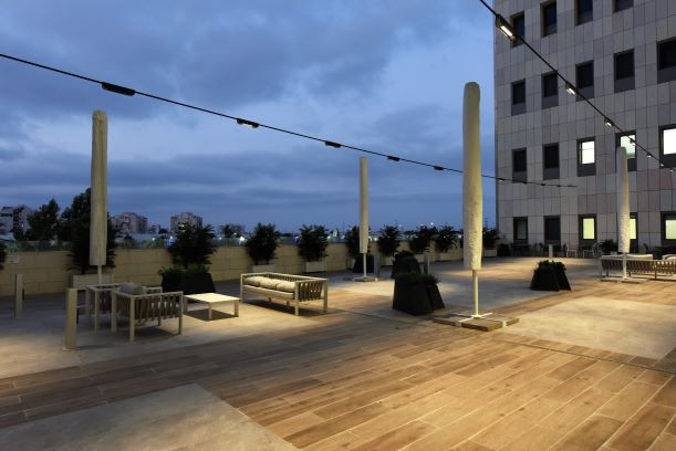 המרפסת מהצד. גופי התאורה מתוחים על כבלים התלויים בין שני צידי הבניין המקיף את המרפסת