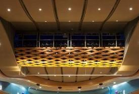 תמונת תקריב של גשר התאורה העילי, מעל למושבי הקהל, פנסי תיאטרון חבויים על הצוג