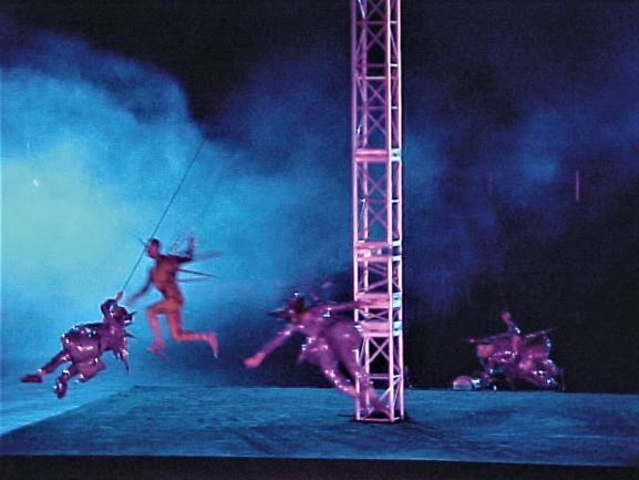 רקדנים-שחקנים מעופפים באוויר. עשן, ואור כחלחל