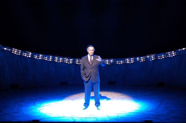 שחקן במרכז הבמה, עיגול אור ממורכז עליו.