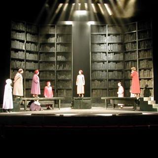 תמונה של כל הבמה מרחוק, המדגישה את עוצמת התפאורה, צבעוניות הבגדים של השחקניות, ואלומות האור הסימטריות.