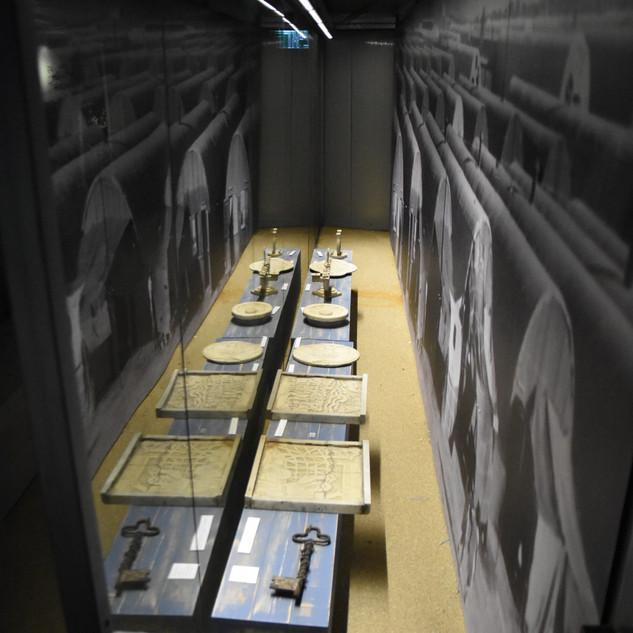 תאורה ייחודית לוויטרינות המוזיאון, אור עדין על המוצגים ההיסטוריים.