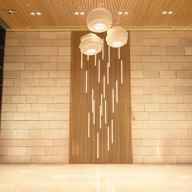 רצועות אור חלבי ייחודי בינות לקורות-עץ בקיר הלובי
