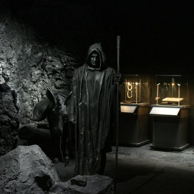 תצוגה של דמות מסתורית עם כובע וגלימה, מוארת באור חלש. בעומק ויטרינות עם מוצגים עתיקים, באור בגוון חמים.