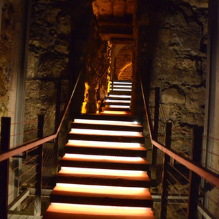 פסי אור חבויים מתחת לכל מדרגה, יוצרים שביל של אור המזמין ללכת בעקבותיו על המדרגות.