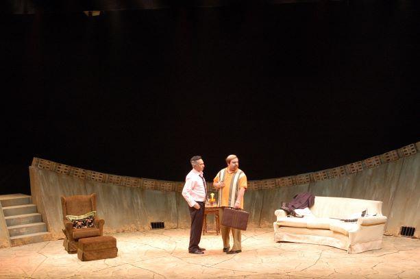 תאורה צהבהבה, הבמה פתוחה, וחלקה הקדמי שטוף אור. שחקנים נראים היטב על הבמה.