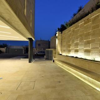 תאורה נסתרת מאירה את קיר הגדר המקיפה את הבניין. משמאל - לובי הכניסה לבית הכנסת.