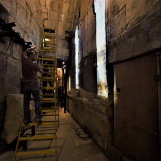 כיווני תאורה אחרונים לפני פתיחת המקום לקהל - פסי אור המדמים חלונות על קיר האבנים התת-קרקעי