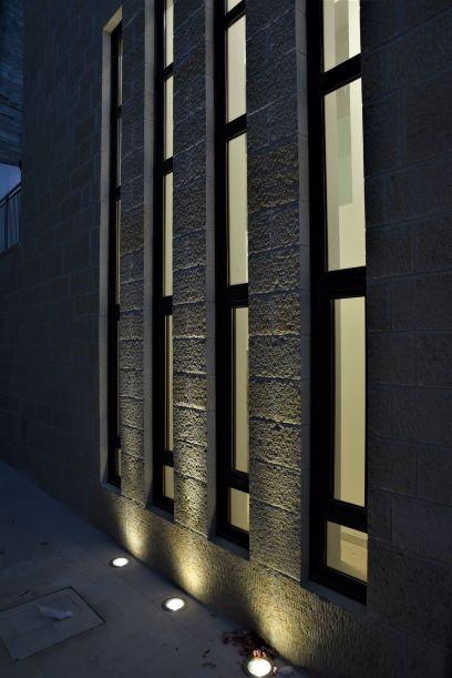 גופי תאורה שקועי-רצפה מאירים את הקיר החיצוני בצורה סימטרית.