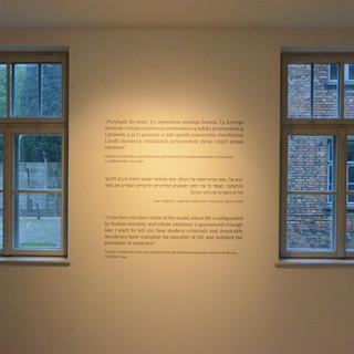 קיר בין שני חלונות. מבחוץ אור אפרפר ומנוכר. הקיר מואר בכתם אור רך, המדגיש את המילים הכתובות עליו