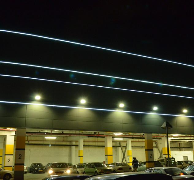 פסי אור על קיר החניון מבחוץ. מדגישים את קווי הבניין, יוצרים עניין לעין