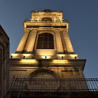 נקודת מבט מתחתית המגדל כלפי מעלה, גופי התאורה הקטנים נטמעים בין קווי המתאר של המגדל, מאירים כלפי מעלה.