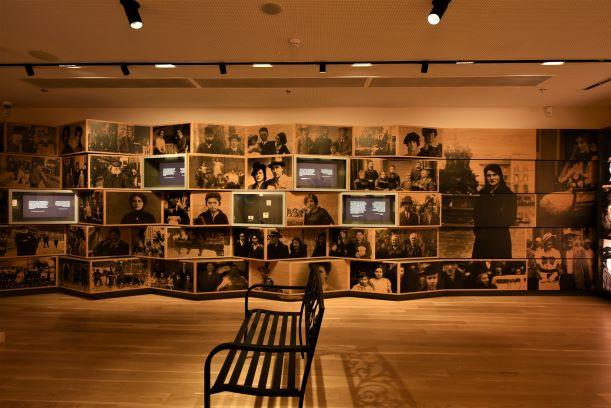 קיר מעוצב עם תמונות בצבע ספיה, אור רל על הקיר ועל הספסל הממוקם בקדמת הפריים.