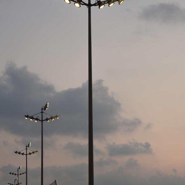 תמונה מקרוב של גופי התאורה הגבוהים, על רקע שמיים אפורים