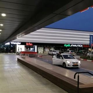 גופי תאורה שקועים בתקרה, המדגישים את קו הכניסה לחנויות, ובמרחק ארבעה פסי תאורת לד המדגישים את המבנה כולו