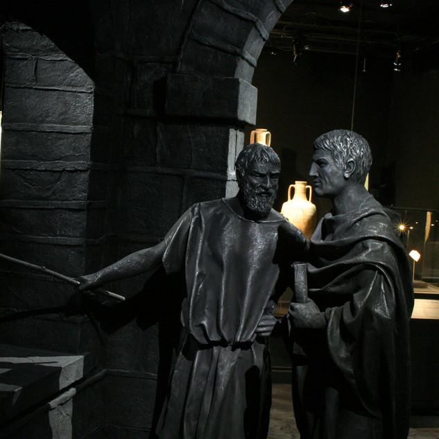שני פסלים של דמויות תקופתיות, מוארים באור עדין.