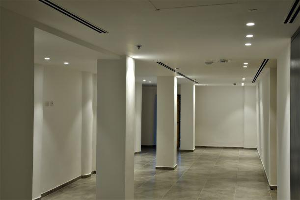 לובי המעליות. פאטרן א-סימטרי של גופי תאורה בתקרה. אור לבן ומשחק של צללים על הרצפה.