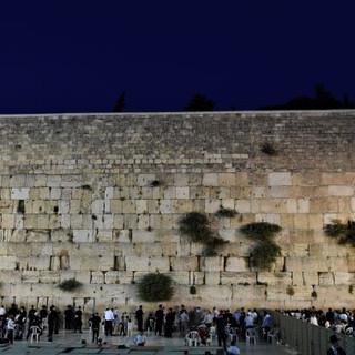 שני איזורי התפילה של הכותל המערבי, בשעת ערב. תאורה עדינה על האבנים העתיקות