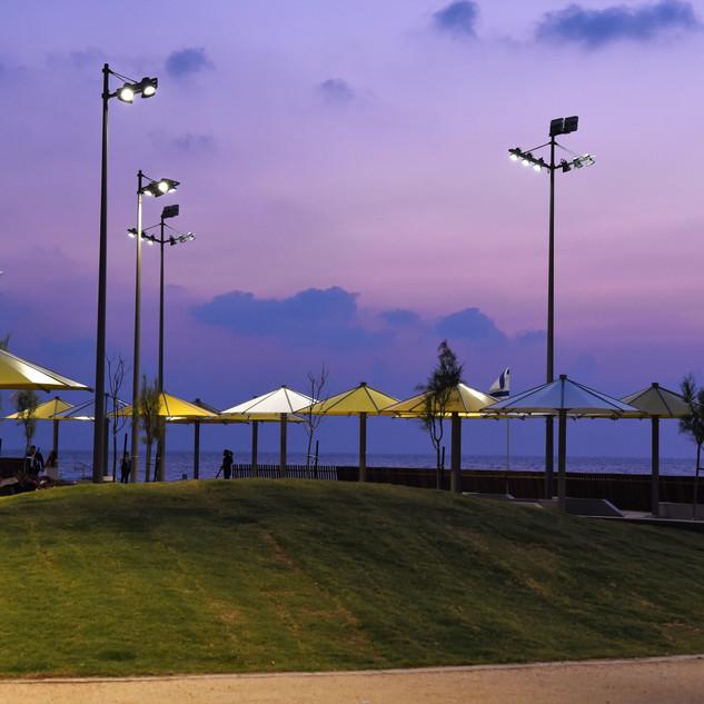 עמודי התאורה המעוצבים נראים חלק מהשמשיות והנוף הכללי של החוף, כאן בשעת שקיעה
