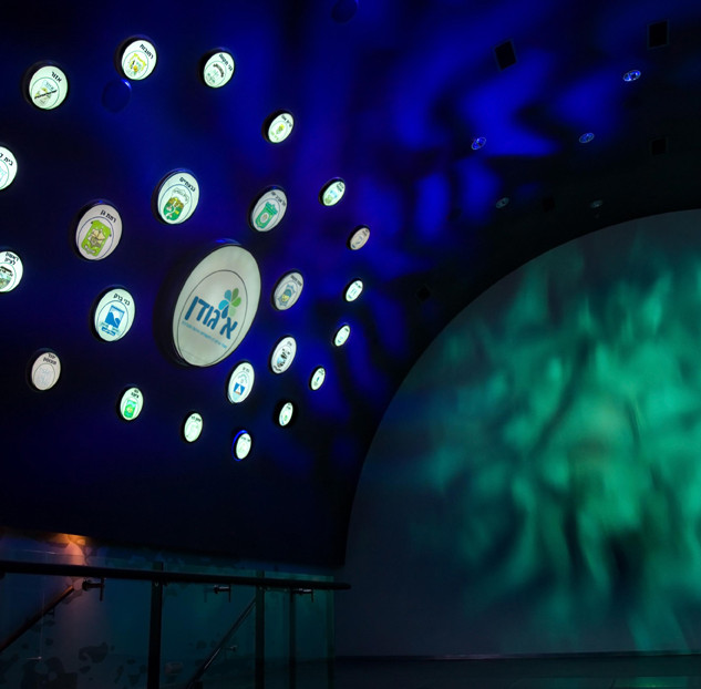 קיר בתצוגה, עיגולים מוארים על רקע של קיר כחול, עם גובו של מים, וקיר באור ירקרק