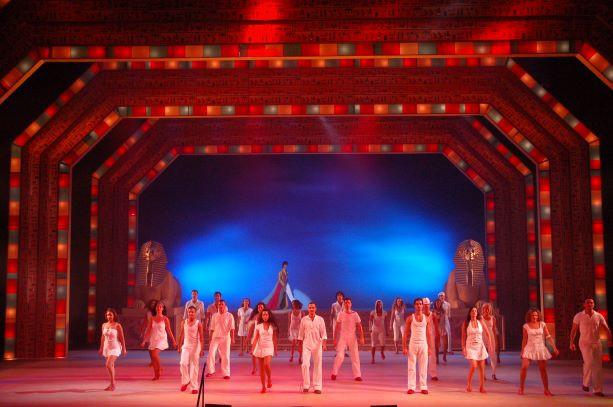 משתתפי המחזמר על הבמה, בעומק המסך האחורי כחול, בקדמת הבמה גוונים רכים של אור