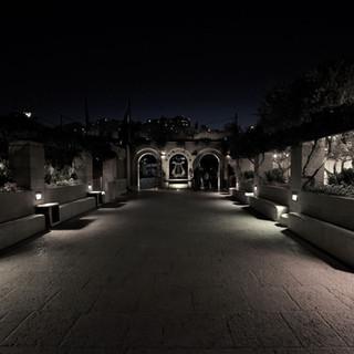 שעת ערב, שביל הכניסה לגן מואר בתאורה המכוונת כלפי השביל, ומדגישה ברכות את הגן סביב