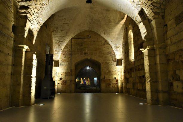 חדר בתוך המצודה הצלבנית. תקרות מעוגלות מקבלות אור המגיע מגופי תאורה על קצות העמודים. בחדר נוצרת אווירה אפלולית עתיקה.
