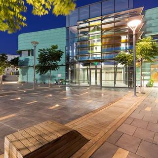 רחבת הכניסה לאולם התרבות, מוארת בפסי-אור, פנס רחוב מעוצב מאיר באור לא-ישיר. צילום: עמית הס