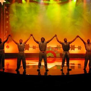 הבמה בצבעוניות של צהוב וכתום. צללית של 4 אמנים מחזיקים ידיים על הבמה.