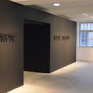 שער הכניסה לתצוגה. התאורה ממוקדת על הקיר השחור, מדגישה את עוצמת המילים הכתובות עליו.
