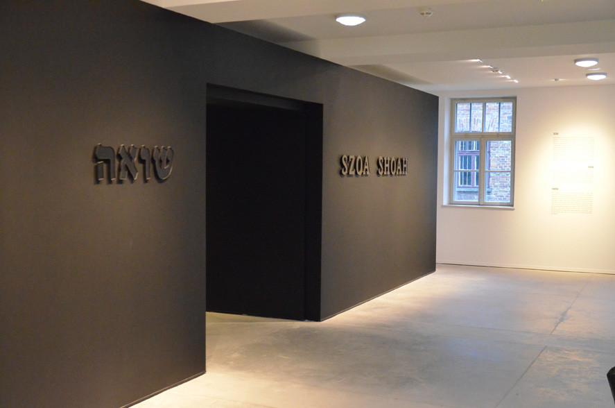 """שער הכניסה השחור למרכז המבקרים באושוויץ. אור בהיר, המדגיש את הכיתוב """"שואה""""."""