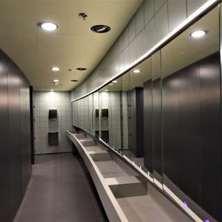 שירותים. תאורה נסתרת מעל המראה וגופי תאורה עגולים סימטריים